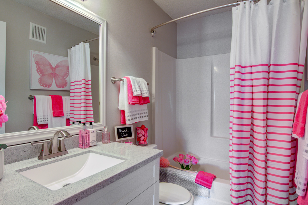 Bathroom sink and shower with pink colored decor.