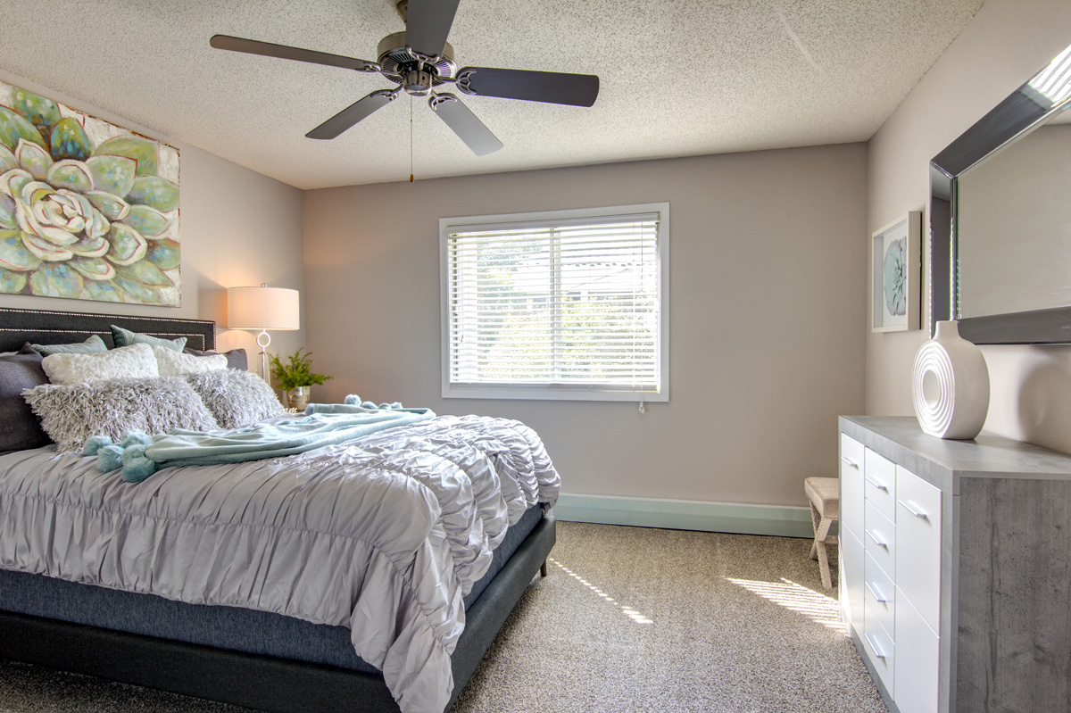 Bedroom with queen bed, ceiling fan, and decorative decor.