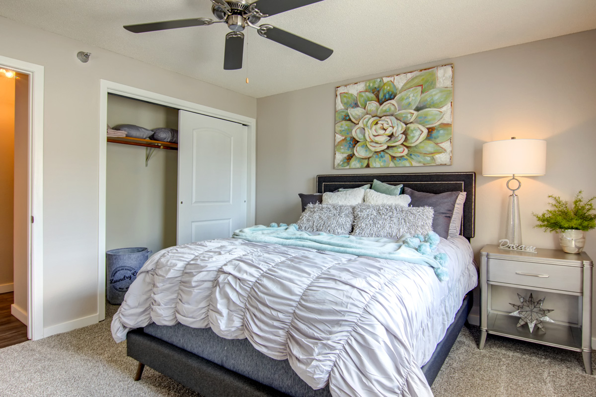 Bedroom with queen bed with closet and ceiling fan.