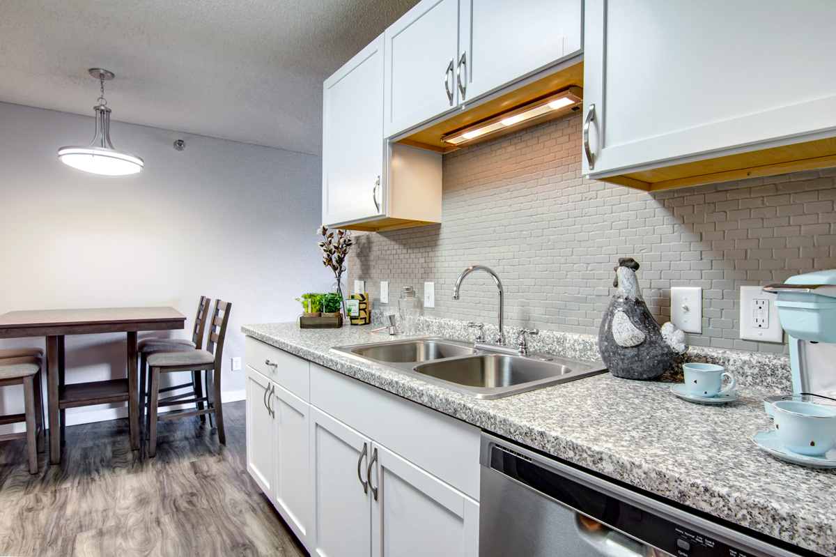 Galley kitchen with white cabinets and stainless steel appliances and dining table.