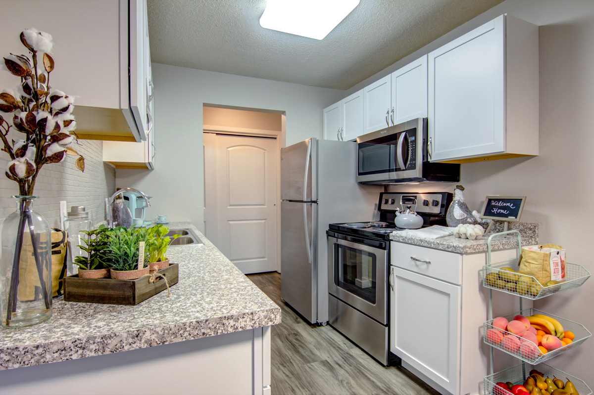 Galley kitchen with white cabinets and stainless steel appliances.