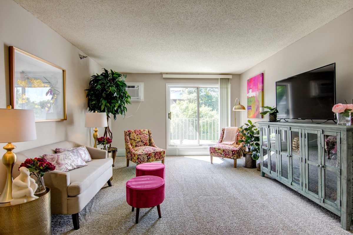 Colorful living room with couches, decor, a television, and a view of a balcony.