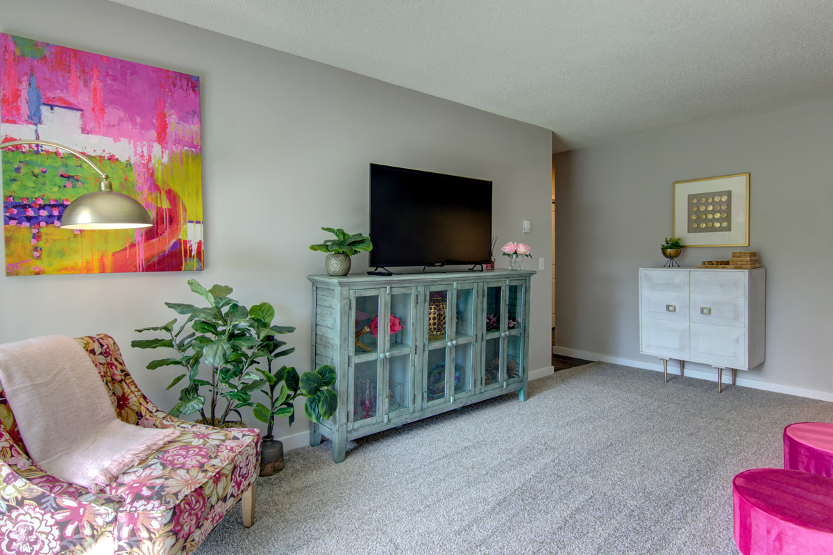 Living room with television and various artwork on the walls