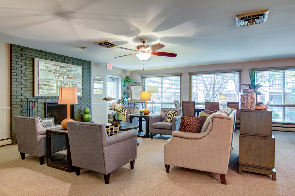 Indoor lounge with grey couches, colorful lamps, and a dining and reception area.