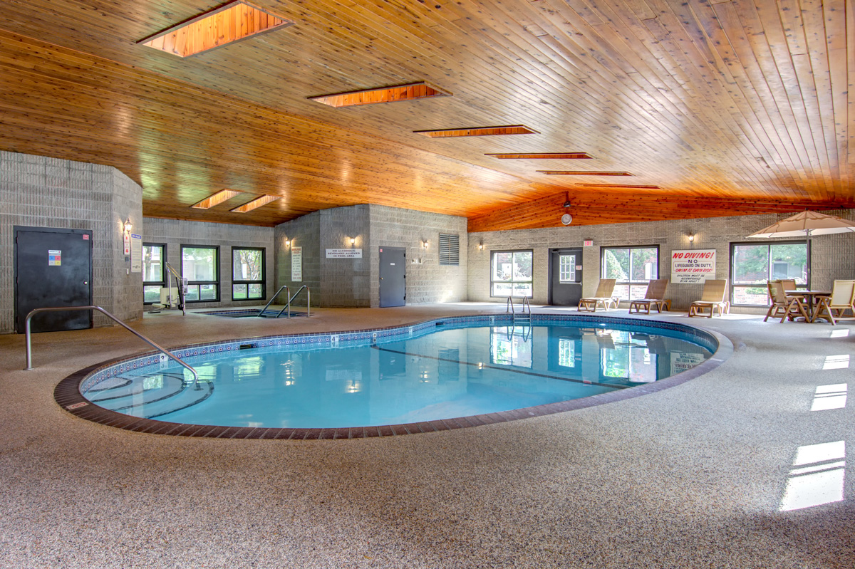 Indoor pool with Jacuzzi and skylights above