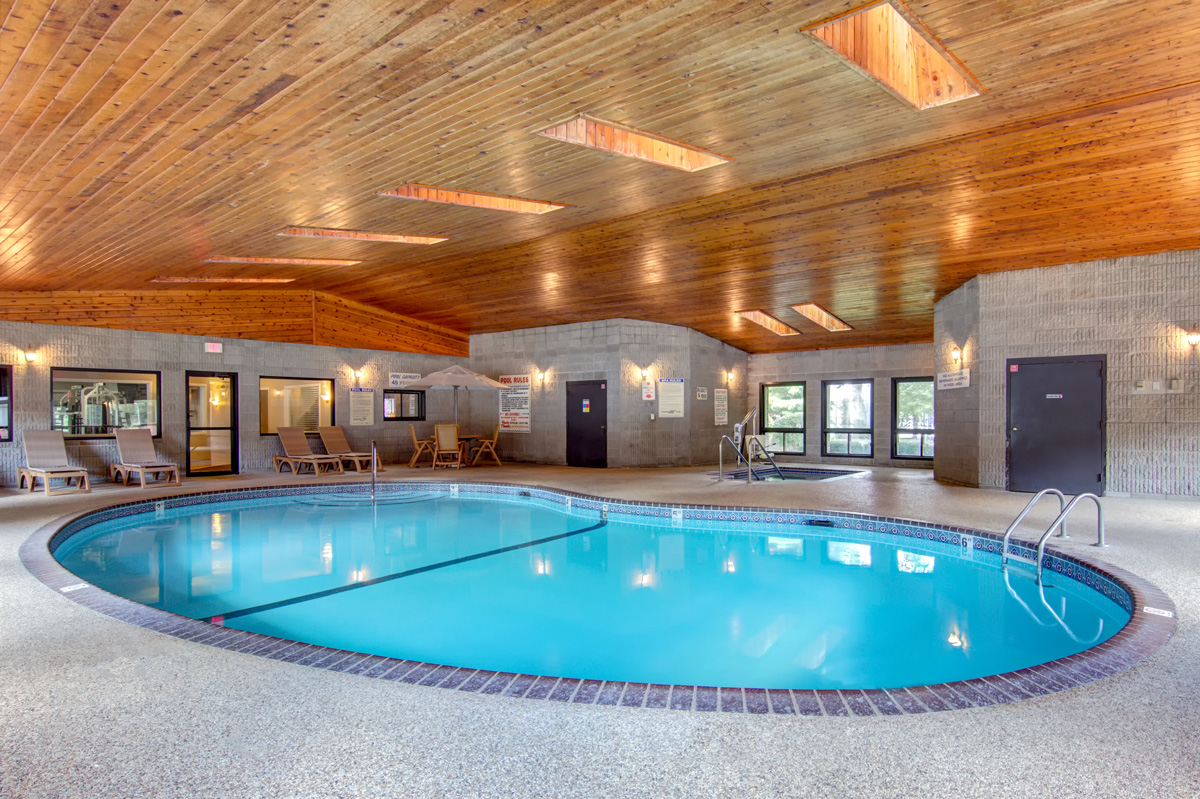 Indoor pool with Jacuzzi and skylights above and loungers surrounding