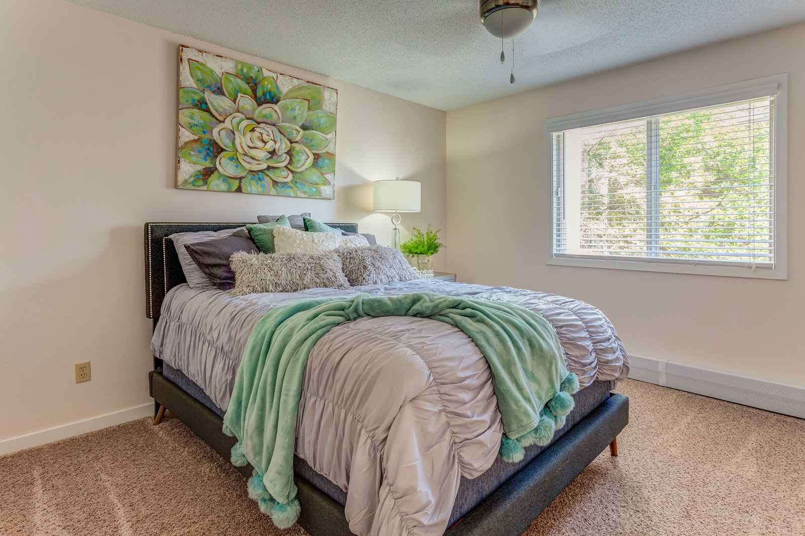 Carriage Oaks spacious bedroom with bed and green and grey decor.