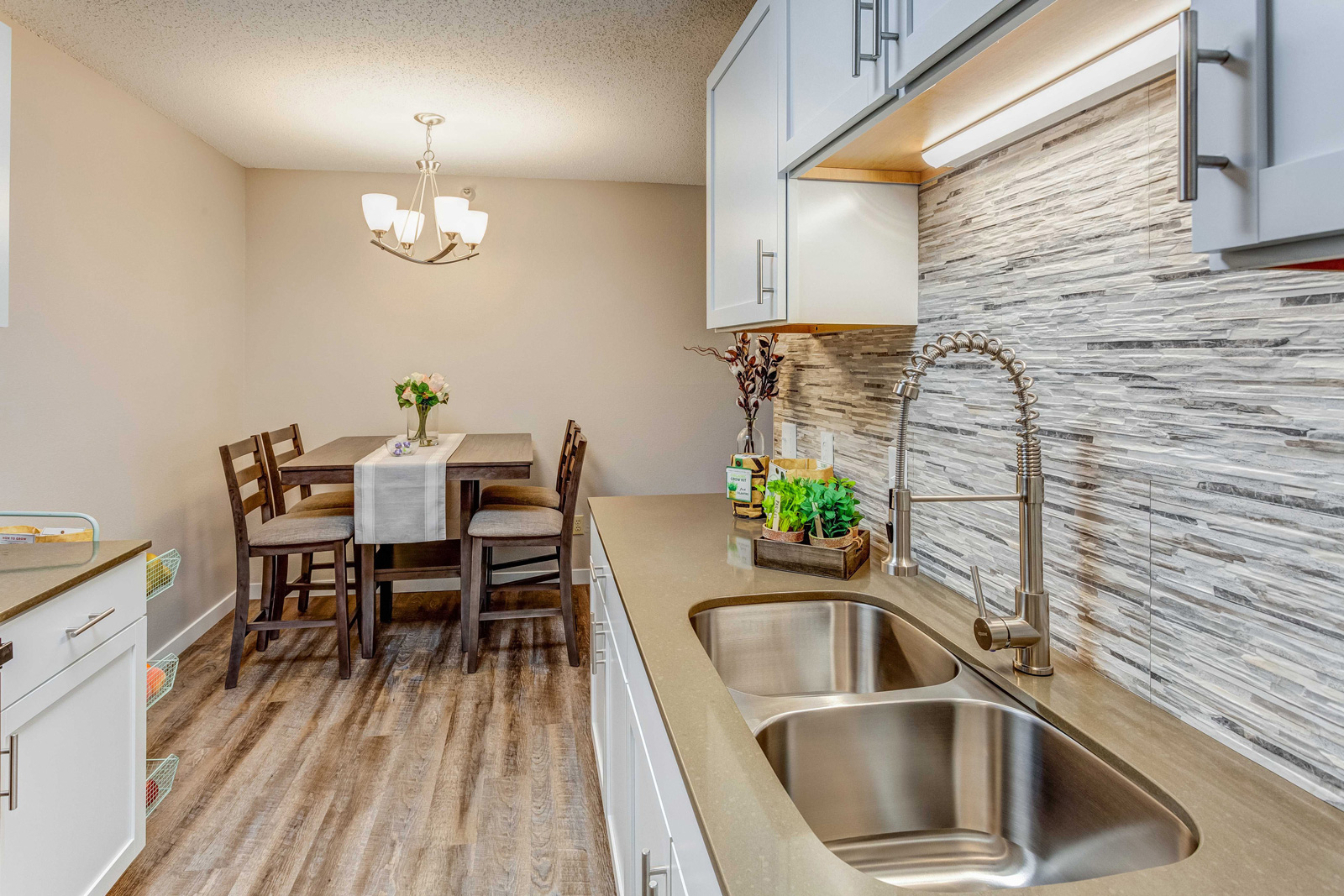 Carriage Oaks kitchen sink with updated backsplash and dining room view.
